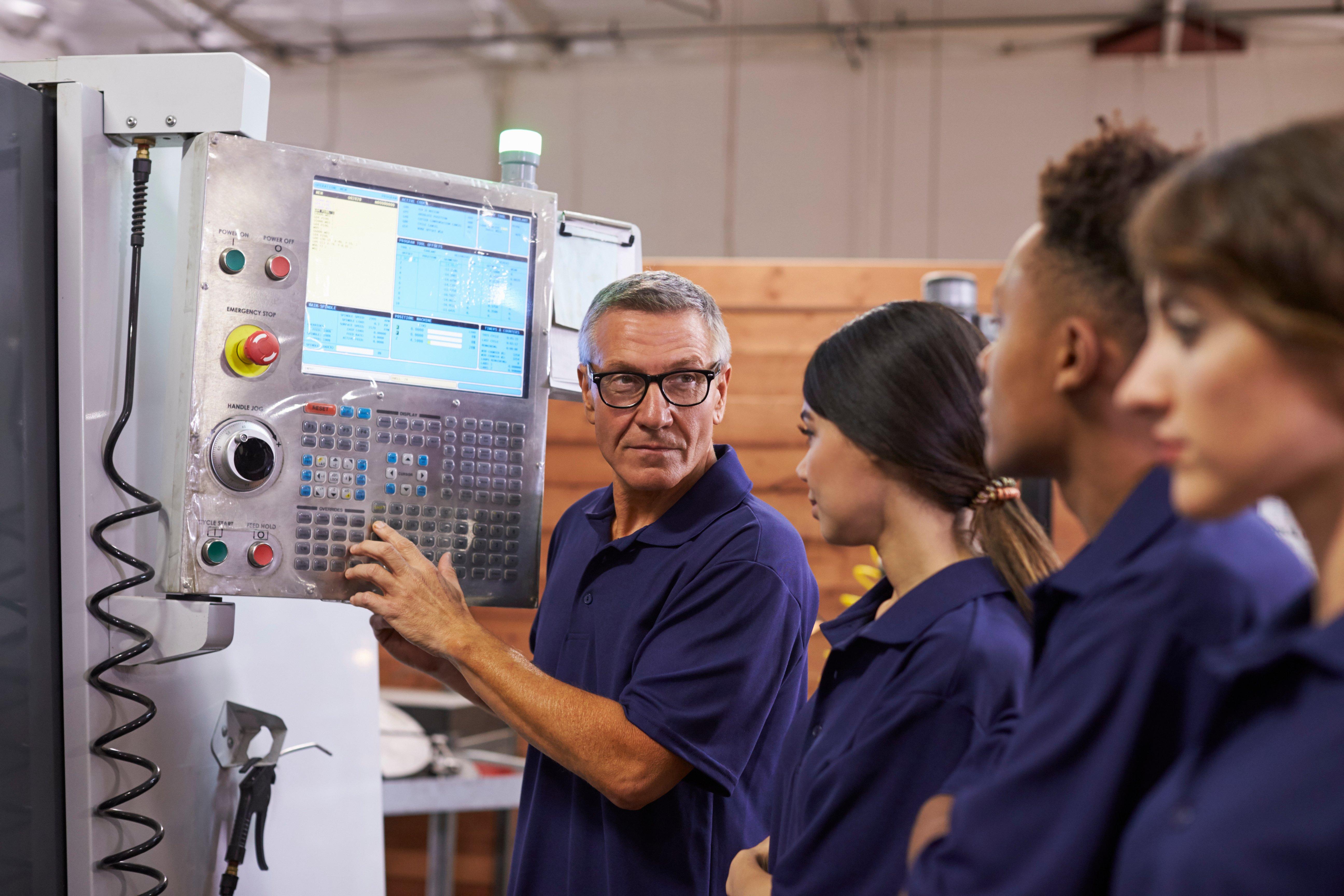 engineer-training-apprentices-on-cnc-machine-PTK2L3S